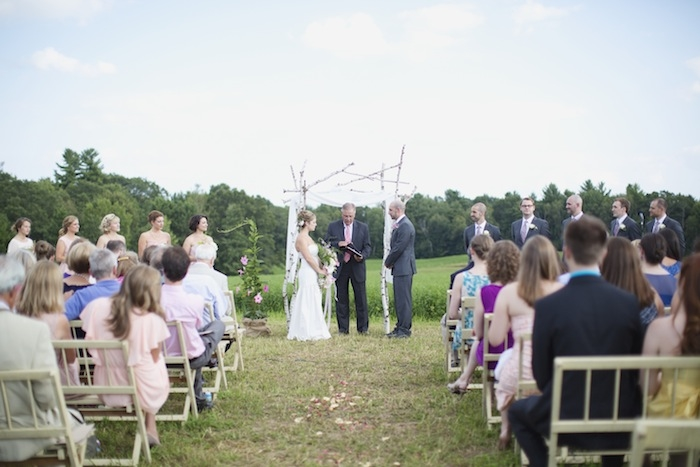 Outdoor ceremony with DIY birch arch