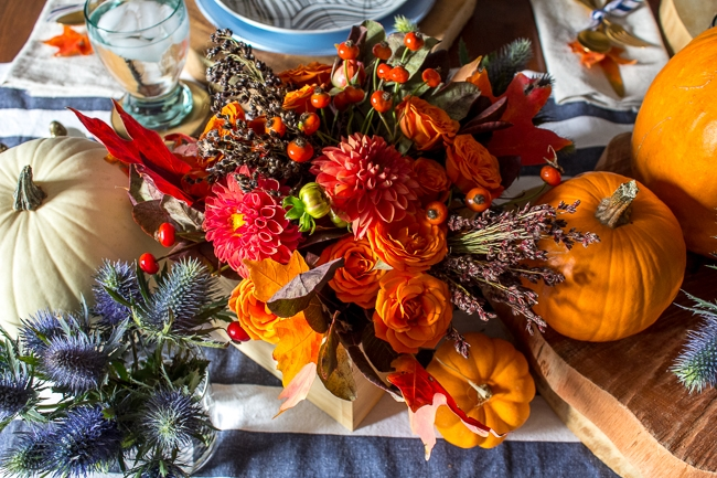 Fall centerpieces with dahlias, broom corn, thistle, and pumpkins.