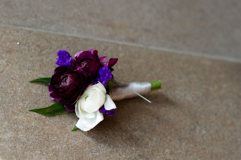 Purple and white ranunculus boutonniere